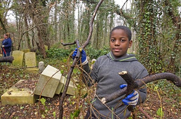 Amir Abdul Mateen, 11, works to clear underbrush at Evergreen Cemetery on March 2. - SCOTT ELMQUIST