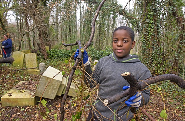 Amir Abdul Mateen, 11, works to clear underbrush at Evergreen Cemetery on March 2. - SCOTT ELMQUIST