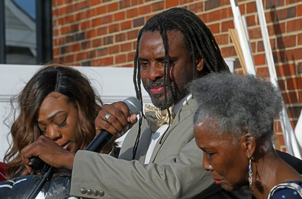 Iman Shabazz remembers his cousin Malik Banks while flanked by Tyler Johnson, the mother of the victim's unborn child, at left, andBanks' great-aunt Diane Hall. - SCOTT ELMQUIST