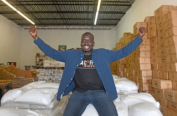 University of Richmond graduate Manyang Kher shows off 734 Coffee beans. The profits help pay for scholarships for Sudanese refugees in Ethiopia. - SCOTT ELMQUIST