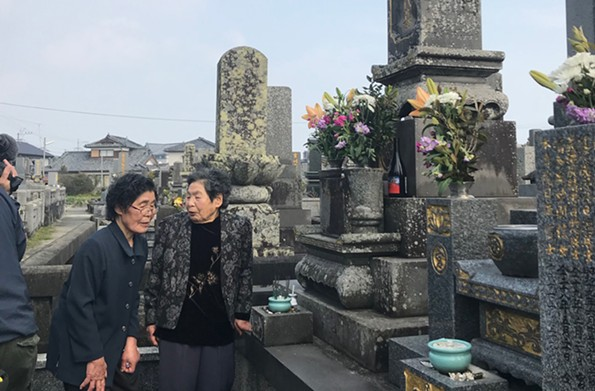 Sisters Yurie Murata and Sumie Miyazaki led Regina Boone to towering stone memorials that featured her grandfather's name in the seaside village of Minamishimabara. - REGINA H. BOONE