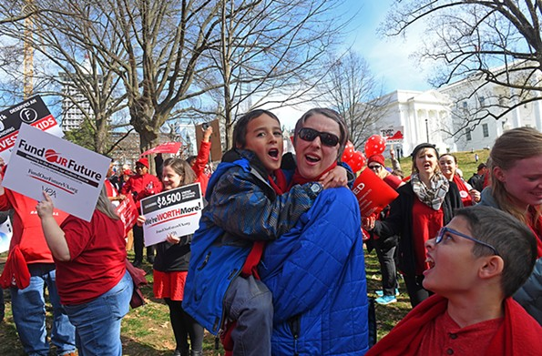 """Educators rallied at the Capitol Bell Tower on Jan. 27. """"Ideally, we would be having Red for Ed rallies all the time,"""" says Lara Dos Passos Coggin, pictured with her son Ignacio Angeles Coggin. """"Anything to bring a united voice in front of legislators."""" - SCOTT ELMQUIST"""