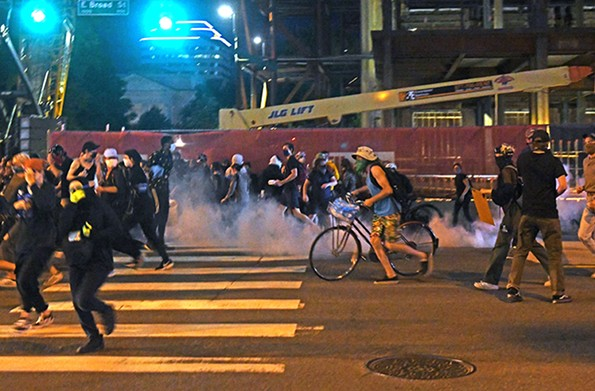 Protesters scatter after police threw tear gas into the crowd near City Hall on Sunday evening. - SCOTT ELMQUIST