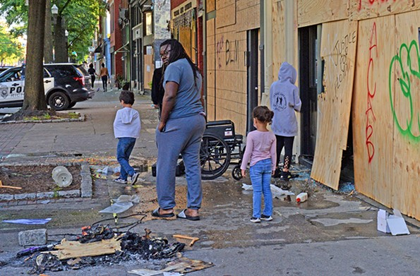 People survey the damage to businesses on Broad Street early Saturday morning. - SCOTT ELMQUIST