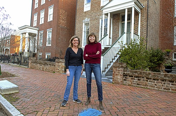 Neighbors Beth Hutchins, at left, and Julie Rautio discuss their historic 19th-century Church Hill homes, the Thomas Hardgrove and Hilary Baker houses, respectively. The adjourningrear yards and gardens should be considerably greener in late April. - SCOTT ELMQUIST