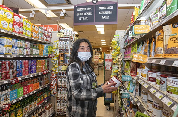 Tina Cho Lickey stocking shelves at Ellwood Thompson's Local Market. As of March 2, Ellwood's had not received any concrete updates from the health department about when exactly workers would be able to receive the vaccine. - SCOTT ELMQUIST