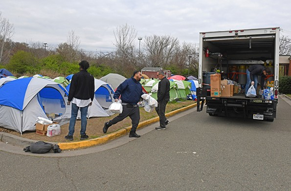 Volunteers from Blessing Warriors load trucks with supplies on March 18, the day Camp Cathy was dismantled. - SCOTT ELMQUIST/FILE