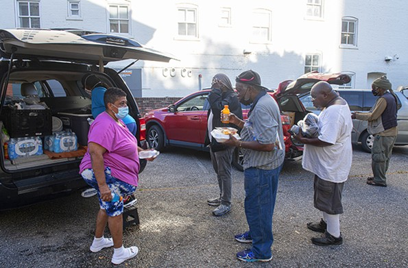 Sneed and another volunteer deliver meals in the parking lot of St. Peter Catholic Church on E. Grace Street. - SCOTT ELMQUIST