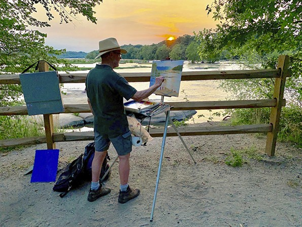 A man paints the river at sunset.