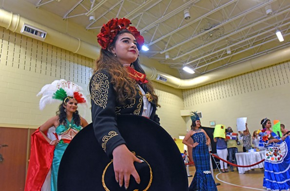 Isabel Gallegos models a Mexican Charro outfit during the Miss Hispanidad talent show May 6 at Ramsey Memorial United Methodist Church. Behind her Thalia Gomez, at left, represents Mexico, Julia Reyes wears a gown made of traditional handcraft fabric of Guatemala and Stefany Reyes, at far right, wears a folkloric-style dress of Honduras. - SCOTT ELMQUIST