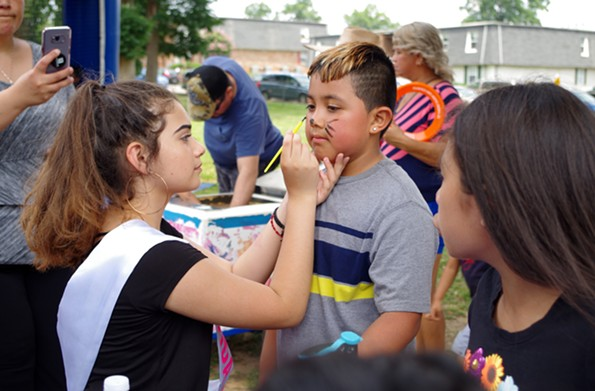 Isabel Gallegos face paints a young attendee at the LaMancha Apartments. - TORI MULLER