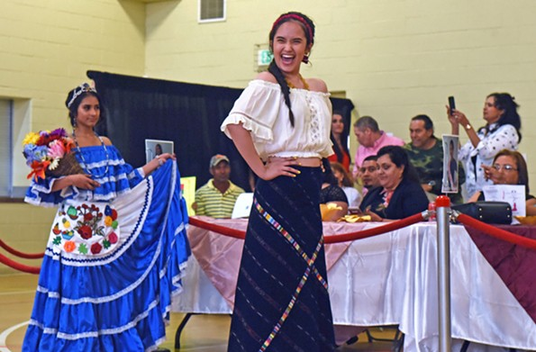 "Stefany Reyes wears a blue and white dress in the Honduran folkloric style and Yasmin Paredes wears the traditional clothing of Guatemala. Paredes says if crowned, she would speak up about the opposition to immigrants, asking ""what have they done wrong?"" - SCOTT ELMQUIST"