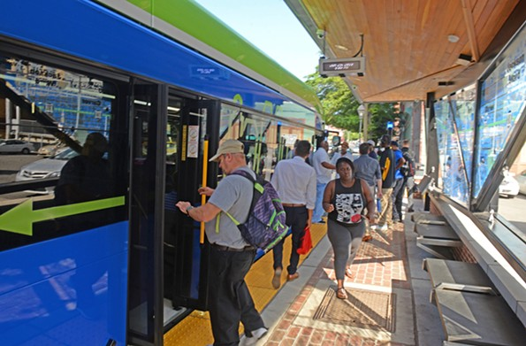 Passengers enter and exit a Pulse bus at Rocketts Landing , the eastern terminus of the new transit system. - SCOTT ELMQUIST