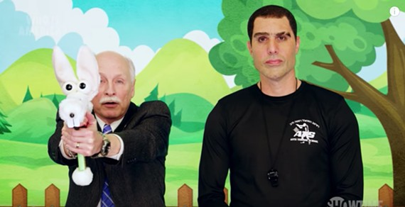 "Activist Philip Van Cleave, president of  Virginia Citizens Defense League, uses ""Puppy Pistol"" to teach children under 4 how to shoot ""bad men"" alongside Sacha Baron Cohen, playing a fake Israeli terrorism expert, on the Showtime series ""Who is America?"""