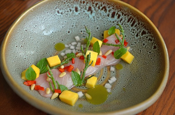 The yellowtail crudo small plate features mango, chilies, Thai basil, kaffir lime oil and pine nuts.