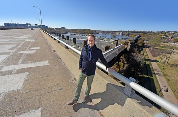 Ted Elmore, the executive director of the BridgePark Foundation, stands on the western edge of the Manchester Bridge. His organization seeks to transform the 1972 structure into the hub of an extended parkway and link the span to Brown's Island at the river's edge, at right of the bridge.