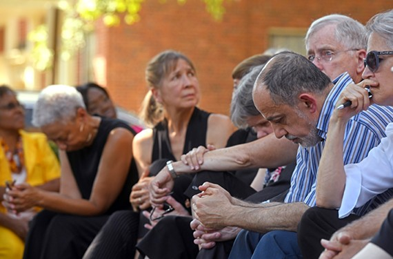 Imad Damaj of the Islamic Center of Virginia bows his head during Witness and Lament, an interfaith vigil Sunday in support of asylum seekers and immigrants at Temple Beth-El.