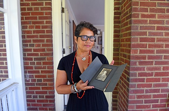 Regina Boone holds a portrait of her grandfather.
