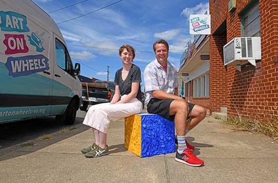 Art on Wheels' Kathleen O'Connor and founder Kevin Orlosky sit on one of their cube bus stop seats created using the contents of Richmonders' pockets.