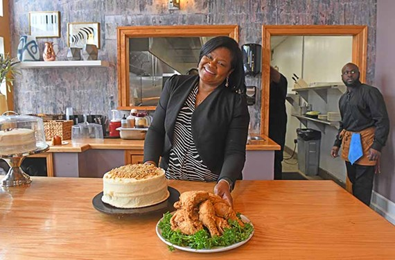 Shane Roberts-Thomas, owner of Southern Kitchen, stands behind a plate of Big Mama's fried chicken and a carrot-cake dessert.