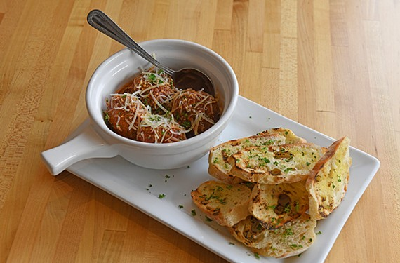 The meatball appetizer ($8) served over a pool of house marinara and shaved Parmesan with a mound of grilled baguette slices.