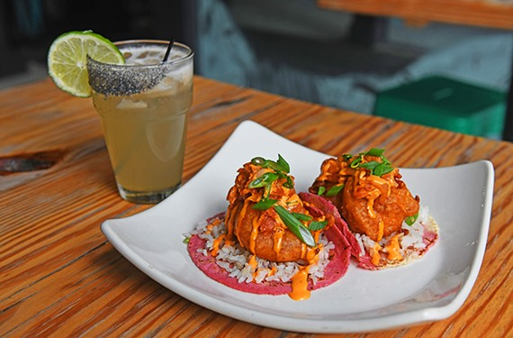 The coconut shrimp tacos feature battered shrimp, spicy mayo, kimchi and seasoned rice.