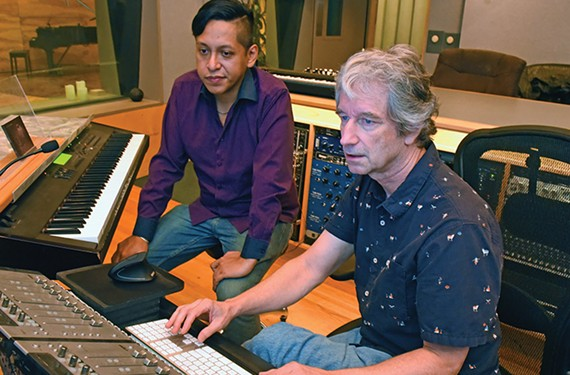 Music producer Alberto Yapur sits next to Carlos Chaffin, a longtime producer and session musician at In Your Ear studio.