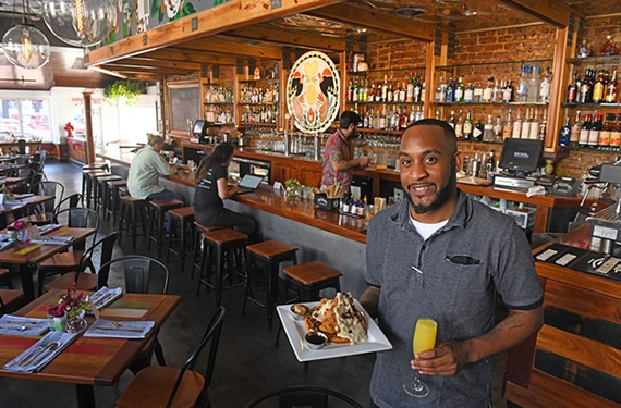 Assistant manager Kevin Alexander at Brunch, the concept by the team behind the Scott's Addition restaurants Lunch and Supper, holds chicken and waffles with a mimosa.