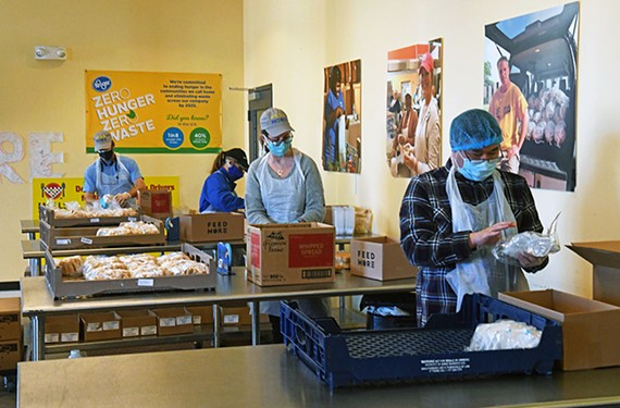 Volunteers pack lunches for Meals on Wheels at Feed More.
