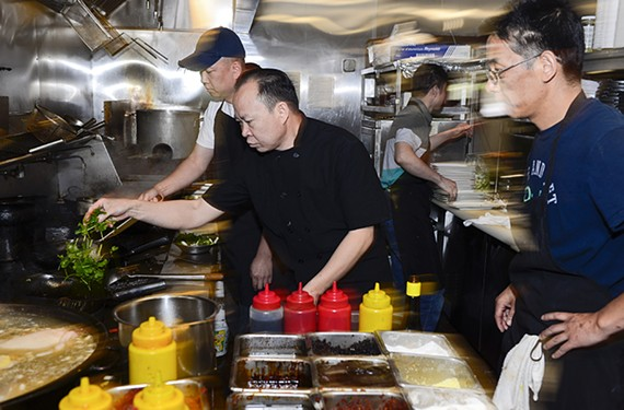 In his busy Short Pump kitchen, Chang demonstrates for his staff exactly how his dishes should be prepared.
