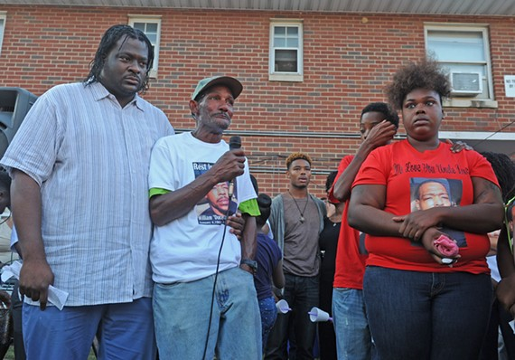 Community activist J.J. Minor stands with Willie Moran, father of shooting victim William Crutchfield, during a vigil on Wednesday.