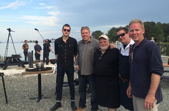 "While ""A Moveable Feast"" host Pete Evans chats to the camera in the background, Paul Kirk, Travis Croxton, Pete Woods, Dylan Fultineer and Ryan Croxton can finally relax after a long day of shooting on the Rappahannock River"