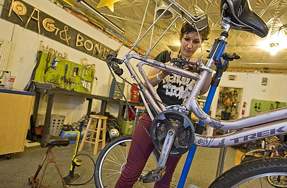 Rag and Bones staff member Sera Stavroula works on a bike in the Scott's Addition co-op. It's staffed by volunteers who offer space and repair help.