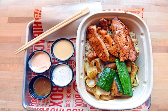 The salmon hibachi box comes drizzled in miso dressing on a bed of fried rice, accompanied by roasted vegetables.
