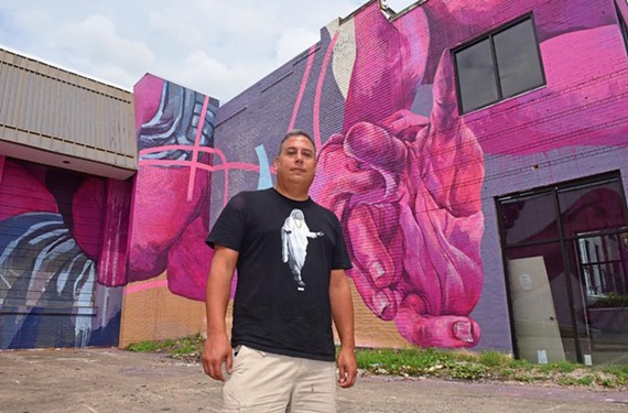 Art Whino's Shane Pomajambo stands in front of a new work by muralist Taylor White at 2614 W. Cary St.