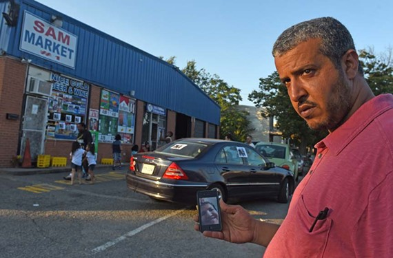 Outside of his brother's store, Sam Market on Nine Mile Road, Mufeed Hafeed holds onto a photo of a FaceTime conversation between his late brother and their mother in Yemen. He says it was the last time they spoke.