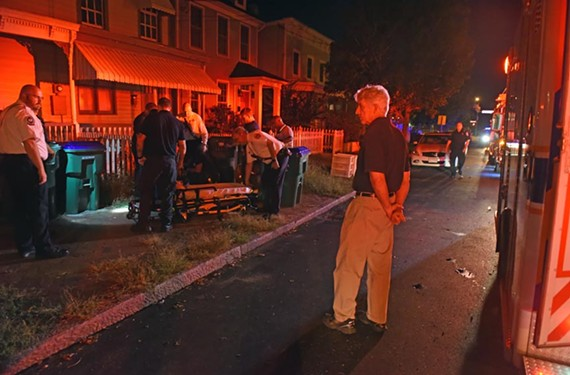 On a ride-along Friday night, Attorney General Mark Herring watches paramedics from the Richmond Ambulance Authority assist a man in Oregon Hill. Herring hopes to raise awareness about Richmond's increasing opiate overdoses.