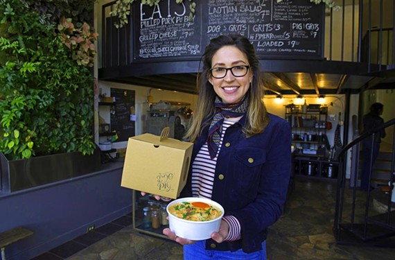 Co-owner Isabel Eckrosh with an order of shrimp and grits at the Dog and Pig Show— the takeout spot will close on Feb. 12.