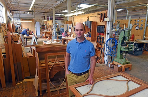 Harrison Higgins V stands in his large workshop.