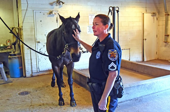 Richmond police officer Amanda Acuff with her partner, Scooter, at the police department's aging horse barn. Supporters hope the city budget will have funds for a new one.