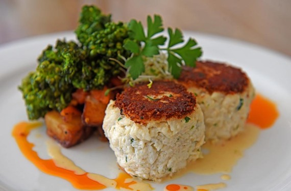 Shore Dog Cafe launches dinner hours with crab cakes surrounded by a basil and red pepper emulsion on its menu.