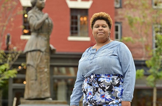 Enjoli Moon, founder and creative director of the Afrikana Independent Film Festival, stands near the new Maggie Walker statue in Jackson Ward. Already this year, Moon was able to bring activist Angela Davis to town for a sold-out VMFA appearance.