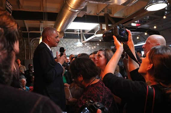 Former U.S. Attorney General Eric Holder speaks to a crowd at Richmond's Blue Bee Cidery in support of Democratic candidates running for the state's top offices.