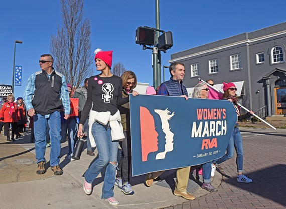 Elizabeth Melson (left) holds a banner with recently elected Governor Ralph Northam on their march through Carytown on Saturday, Jan. 20.
