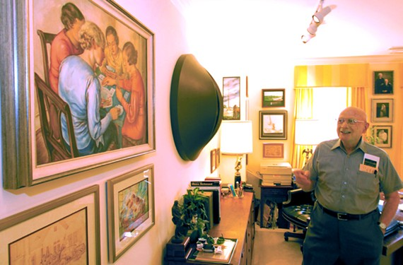 Neil November shows a painting by his mother, noted Richmond artist Sara D. November.