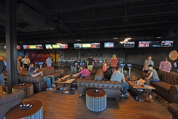Guests try their hands at bowling during River City Roll's soft opening.
