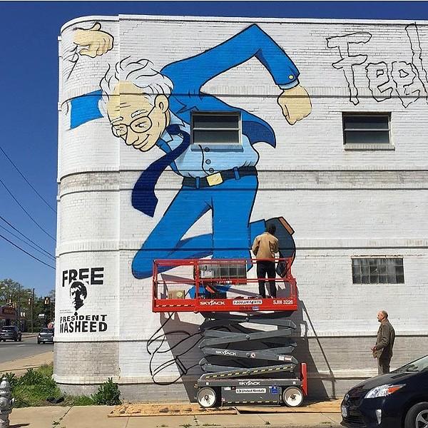 Local artist Mickael Broth works on his Bernie Sanders mural today at 3300 W. Broad Street.