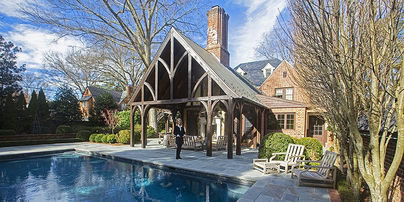 Melinda Hardy, whose grounds will be featured on the Hampton Gardens tour, standsnear the Tudor-inspired porch, part of a 2004 house addition designed by Cox and Associates architects, that provides considerable outdoor living space.