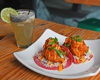 The coconut shrimp tacos feature battered shrimp, spicy mayo, kimchi and seasoned rice.