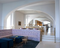 Broad arches, designed by ArchitectureFirm, create an iconic canopy that connects the hotel entry to the rear of the lobby bar, shown here.